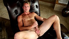 He sits on a black couch fully naked and stroking his cock with excitement