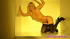 Sexy blonde with a hot body and black stockings poses in a box