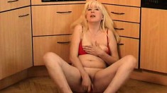 Mature lady Lucinda rubs her nipples and toys her pussy in the kitchen