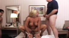 Big Breasted Blonde Nympho Has Three Guys Plowing Her Holes On The Bed