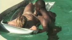 Interracial couple get into the swimming pool to blow each other