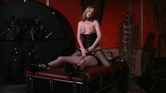 Dominatrix ties her slave down on the table and has her suck boobs